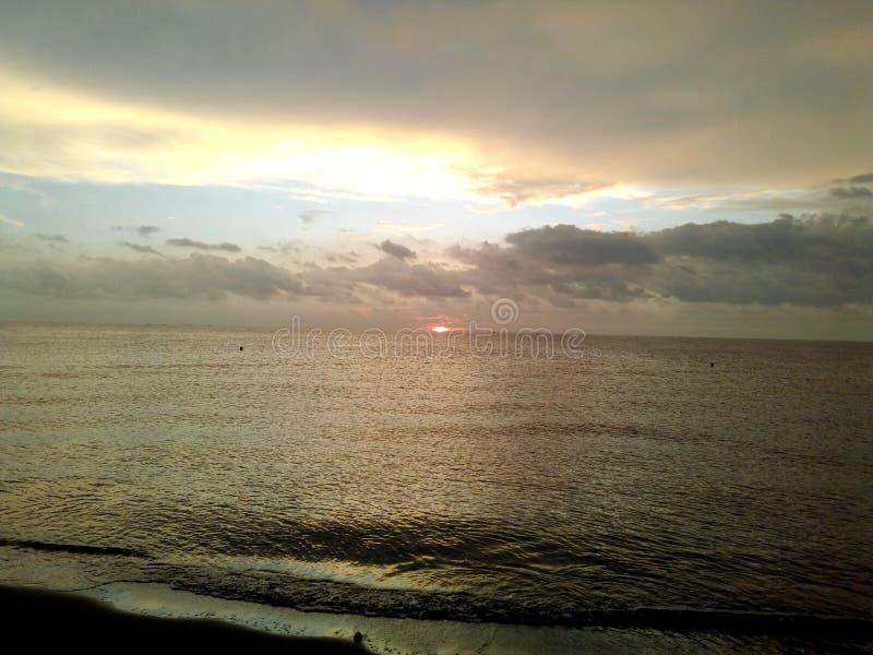 tramonto nascondentesi alla spiaggia fotografie stock