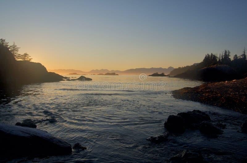 Tramonto nebbioso osservato dalla spiaggia sull'isola della primavera sulla sera calma di estate immagine stock libera da diritti