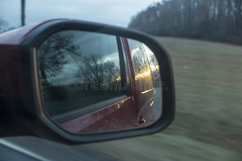 Tramonto nel retrovisore dell'automobile immagini stock