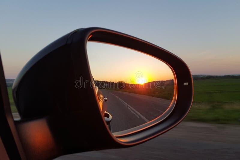 Tramonto nel retrovisore di un'automobile nera Specchi laterali immagine stock libera da diritti