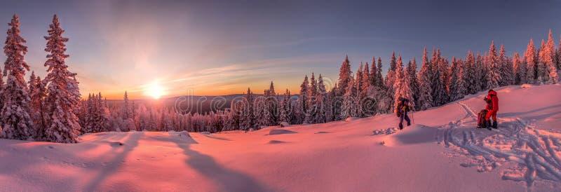 Tramonto nelle montagne nevose, con due sciatori e turisti sul pendio fotografia stock