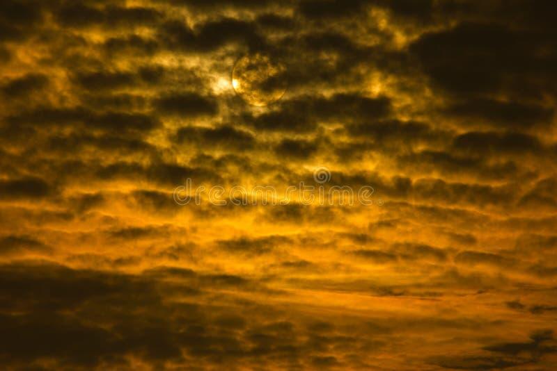 Tramonto o alba drammatico con il cielo dorato e le nuvole nere che formano un estratto con il sole nei precedenti immagine stock libera da diritti