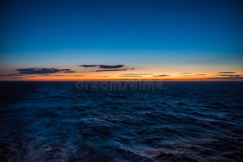 Tramonto, onde e cielo blu sull'Oceano Atlantico fotografia stock libera da diritti