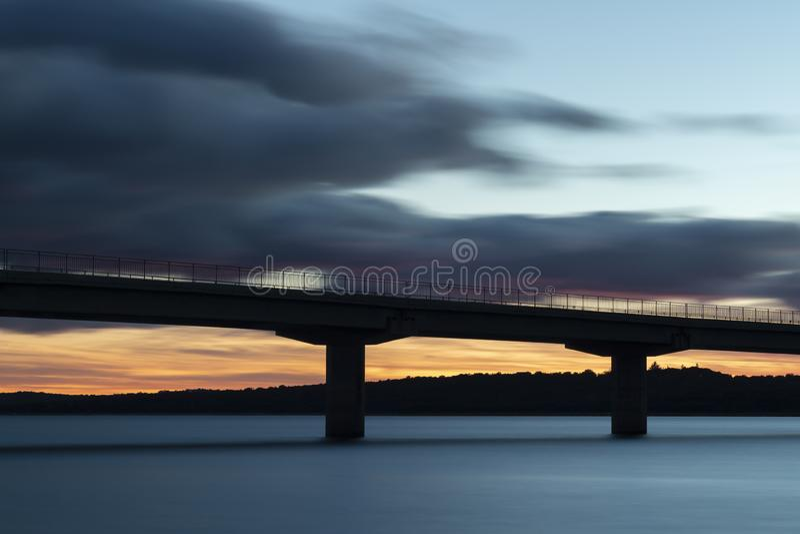 Tramonto piacevole dopo un viadotto che attraversa un lago immagine stock libera da diritti