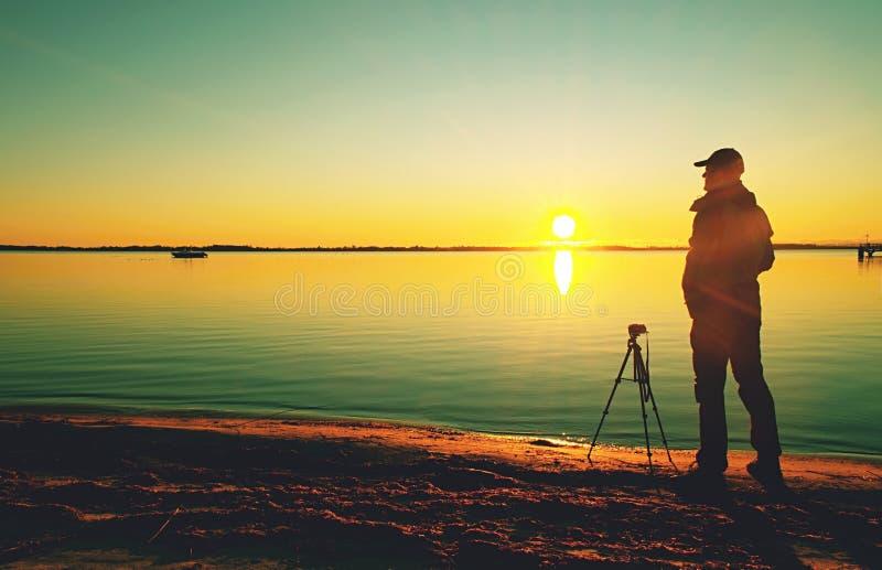 Tramonto professionale del tiro del fotografo con la macchina fotografica sul treppiede fotografia stock