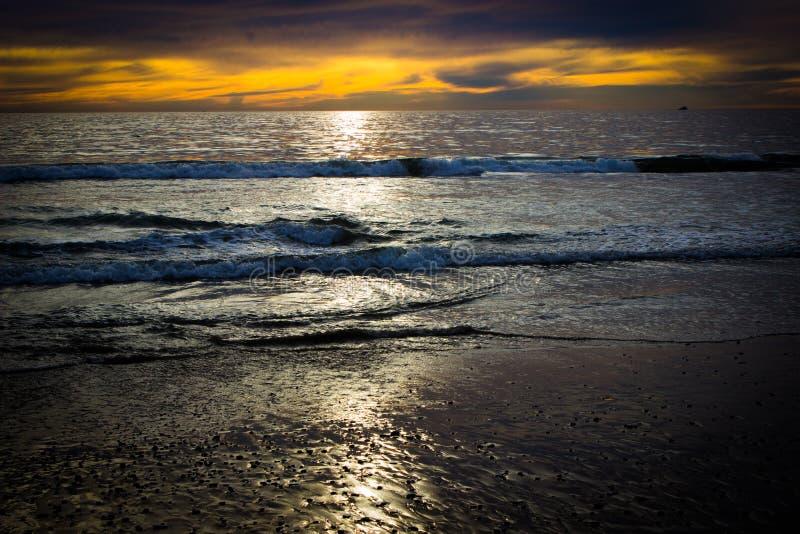Tramonto riflettente dell'oceano Pacifico dalla riva fotografia stock