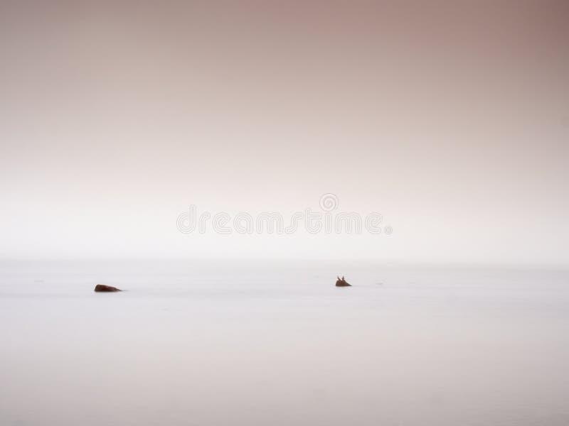 Tramonto rosa alla costa rocciosa del mare Livello dell'acqua regolare ed effetto vago fotografie stock libere da diritti