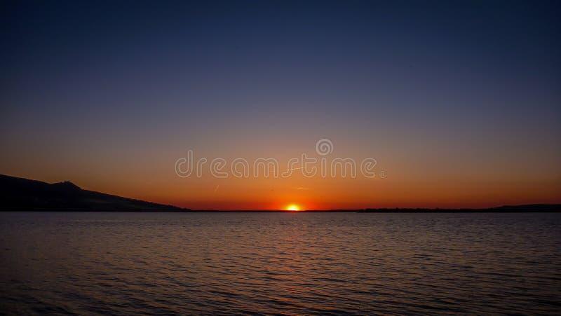 Tramonto scuro sopra Palava, pieno scenici di blu, di rosso, di giallo e di viola sul lago Nove Mlyny vicino a Sakvice immagine stock libera da diritti