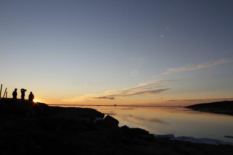 Tramonto sopra acqua con tre genti nell'ombra con whisp delle nuvole fotografie stock