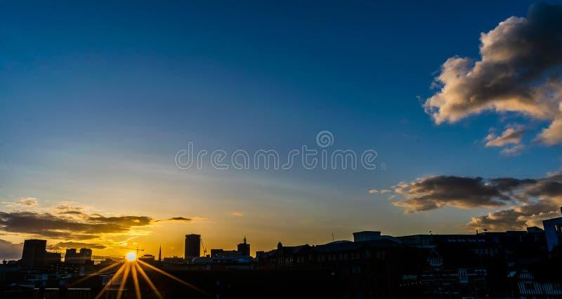 Tramonto sopra Birmingham con i raggi del sole fotografia stock libera da diritti