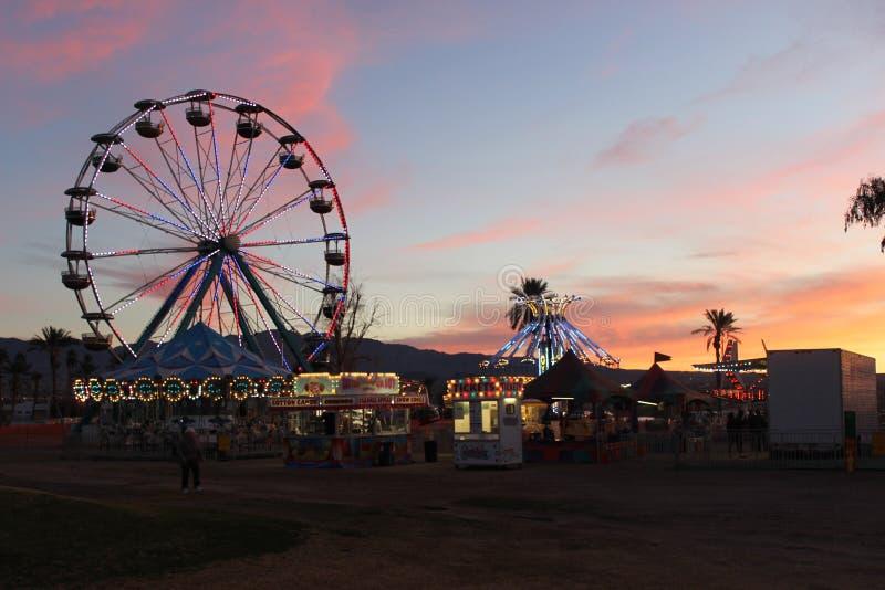 Tramonto sopra Ferris Wheel ed i giri di carnevale fotografie stock libere da diritti