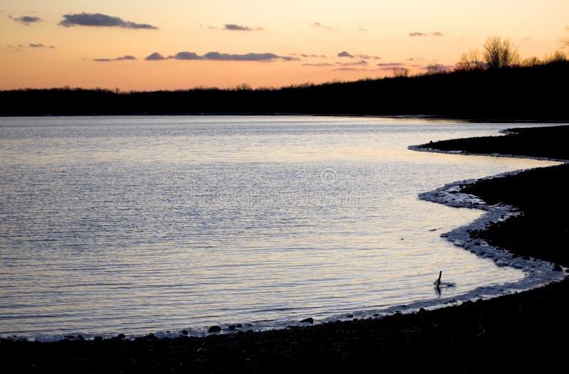 Tramonto sopra il lago nell'inverno fotografia stock libera da diritti