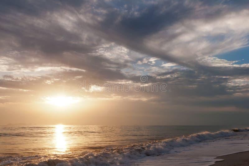 Tramonto sopra il mare ed il cielo nuvoloso immagine stock