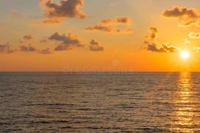 Tramonto sopra il mare in nuvole Il sole proviene dal bordo fotografie stock