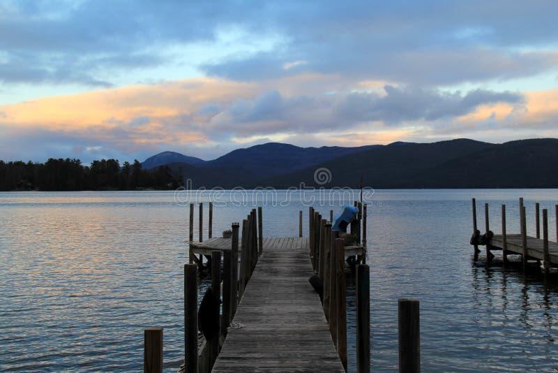 Tramonto sopra l'acqua, con i pilastri di legno lunghi che raggiungono nella distanza fotografie stock