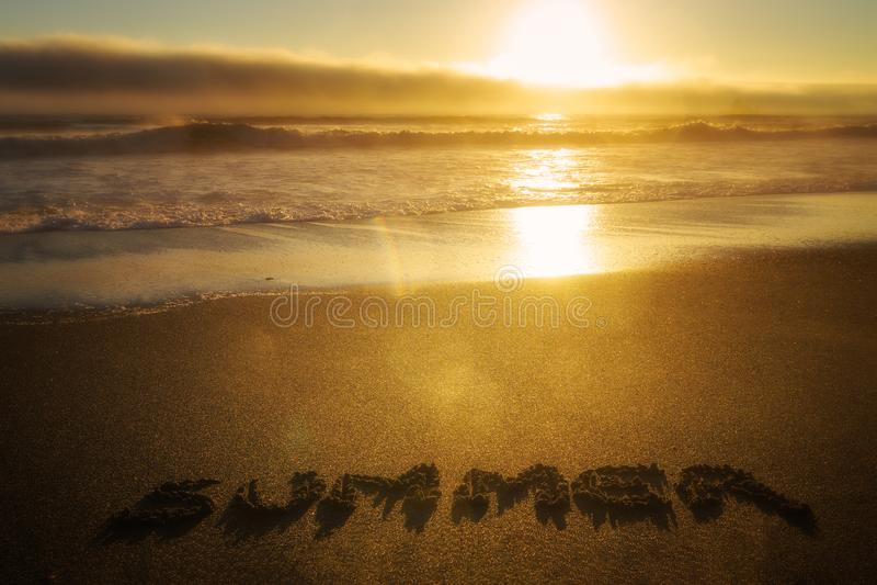 Tramonto sopra l'oceano con l'estate di parola scritta nella sabbia Concetto di stagione fotografia stock libera da diritti