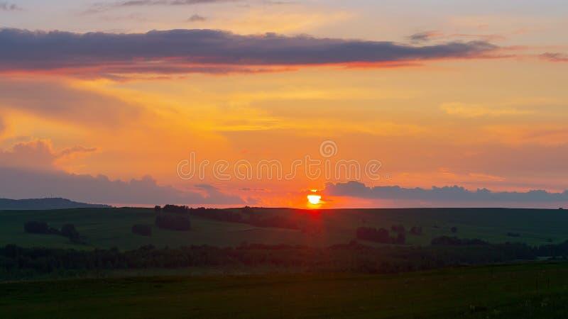 Tramonto sopra l'orizzonte contro il cielo arancio fotografia stock