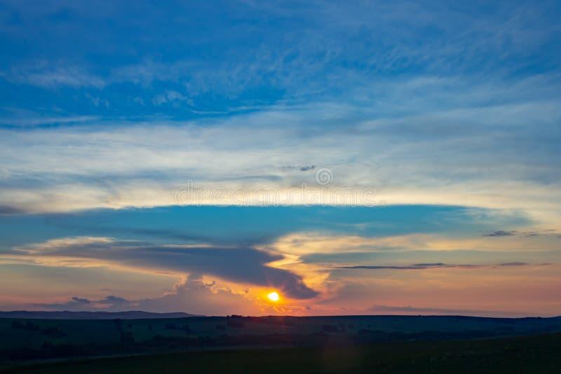 Tramonto sopra l'orizzonte contro il cielo blu fotografia stock libera da diritti