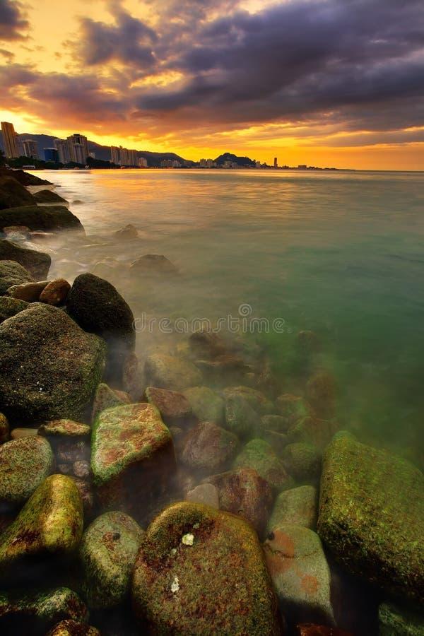 Tramonto sopra la città e l'oceano fotografie stock libere da diritti