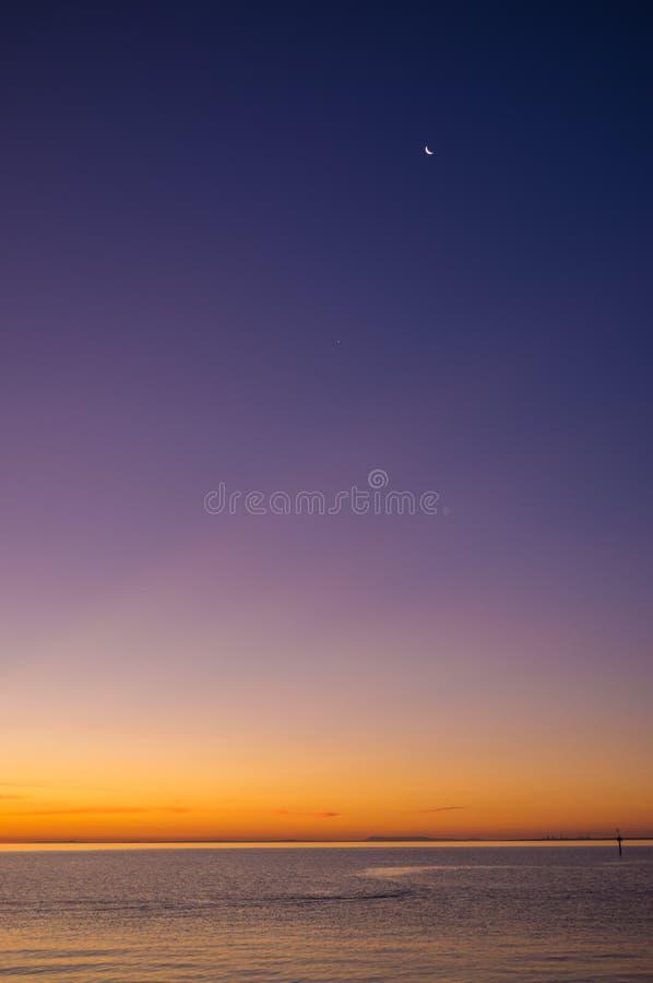 Tramonto sopra la penisola di Mornington con alto alto della nuova luna immagine stock