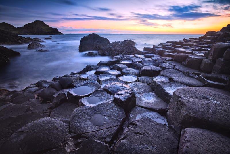 Tramonto sopra la strada soprelevata di Giants di formazione rocciosa, contea Antrim, Irlanda del Nord, Regno Unito fotografia stock libera da diritti