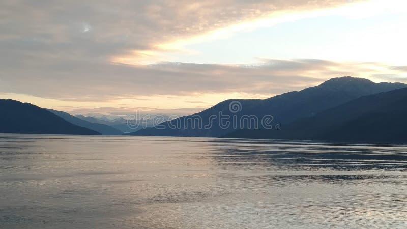 Tramonto sopra le montagne che attraversano l'annuvolamento pesante sull'oceano Pacifico nell'Alaska Stati Uniti d'America fotografia stock libera da diritti