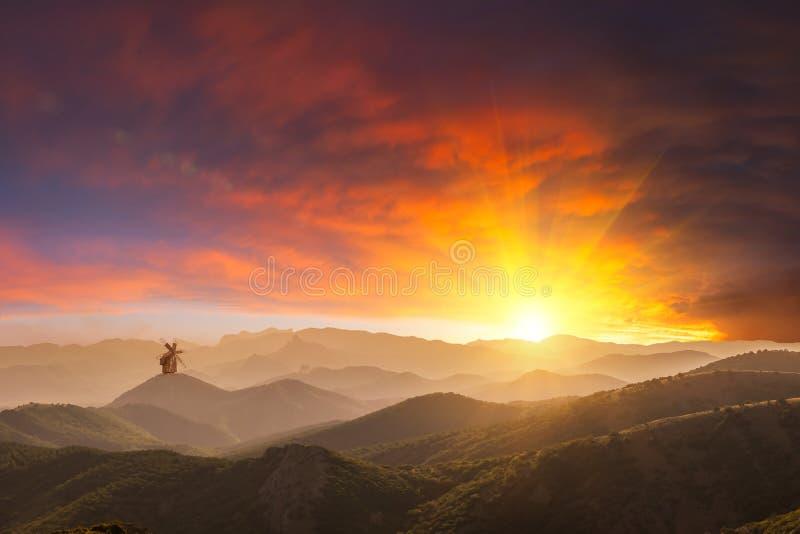 Tramonto sopra le montagne ed il mulino a vento solo fotografia stock