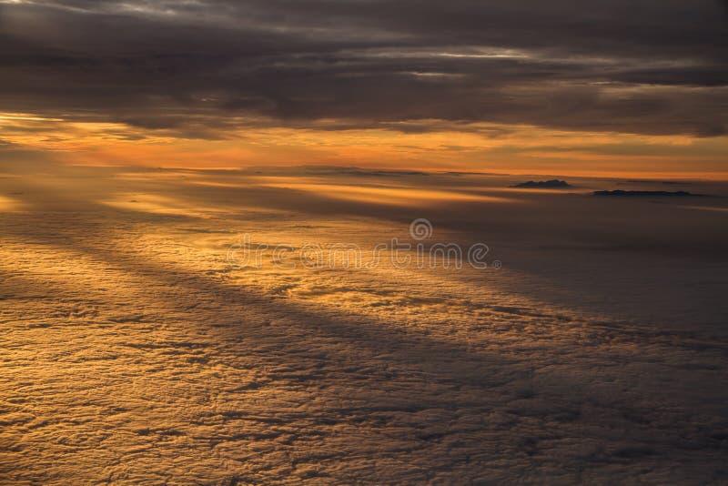Tramonto sopra le nuvole con le cime della montagna dall'aereo immagini stock libere da diritti
