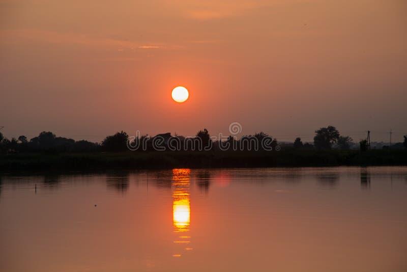 Tramonto sopra un lago calmo - riflessione del sole nell'acqua fotografie stock libere da diritti