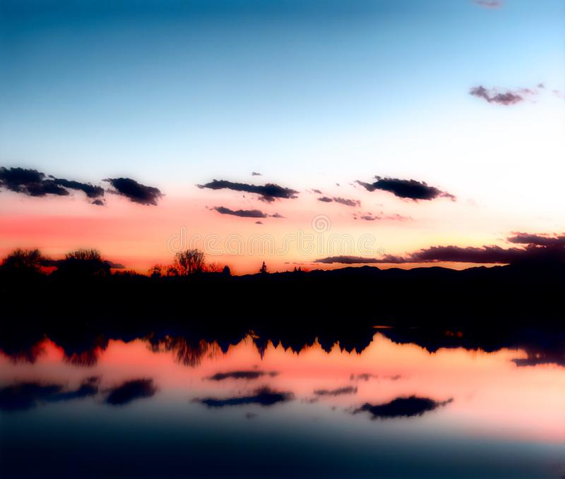 Tramonto sopra un lago con le riflessioni nell'acqua fotografia stock libera da diritti