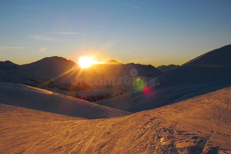 Tramonto sopra una catena montuosa alpina innevata fotografia stock