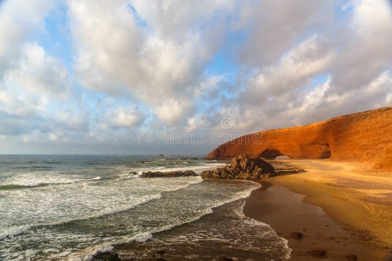 Tramonto in spiaggia di Legzira con l'arco rosso, l'Oceano Atlantico, Sidi Ifni fotografia stock libera da diritti
