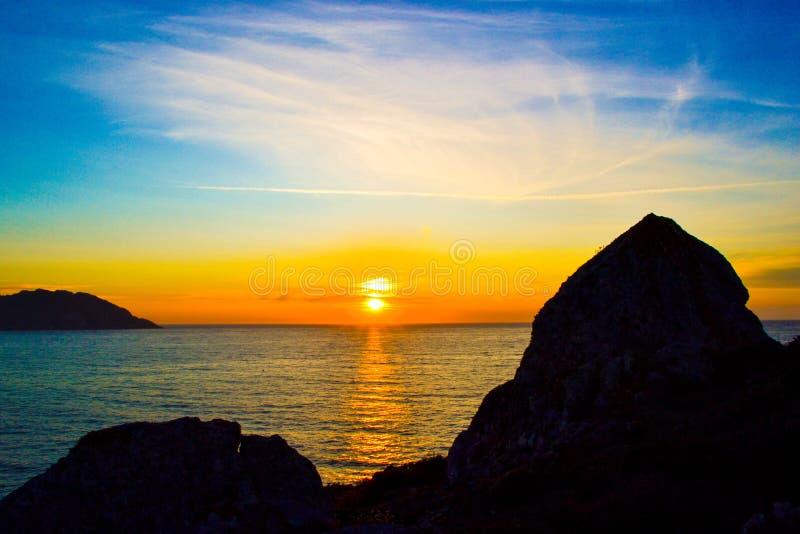 Tramonto stupefacente e variopinto sopra il mare con le rocce scure al fotografia stock libera da diritti