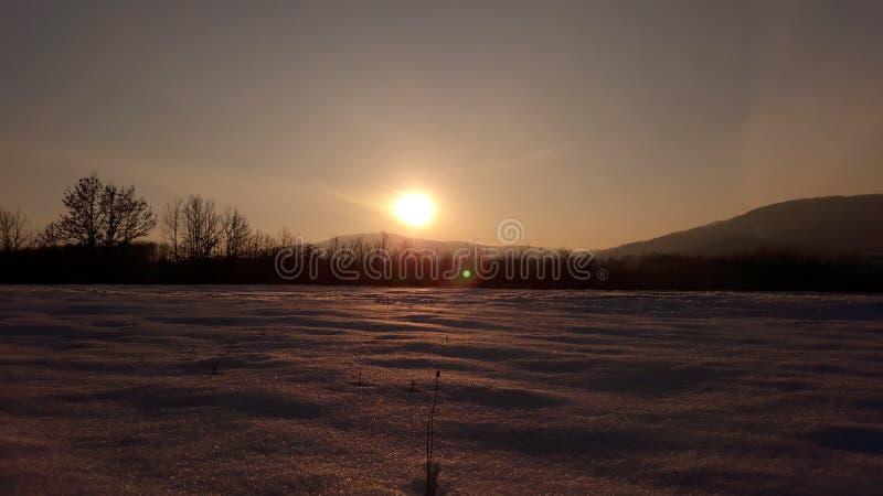 Tramonto sul campo della terra della neve fotografia stock