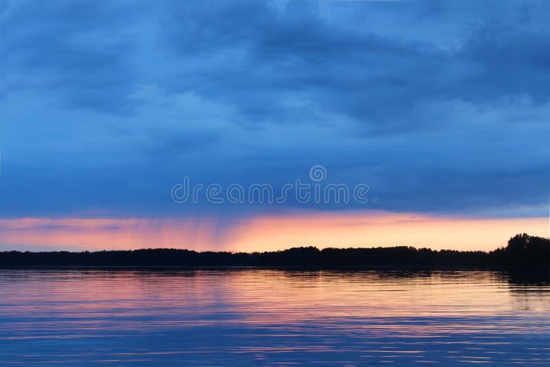 Tramonto sul lago Vuoksa È piccola pioggia sull'orizzonte fotografie stock libere da diritti