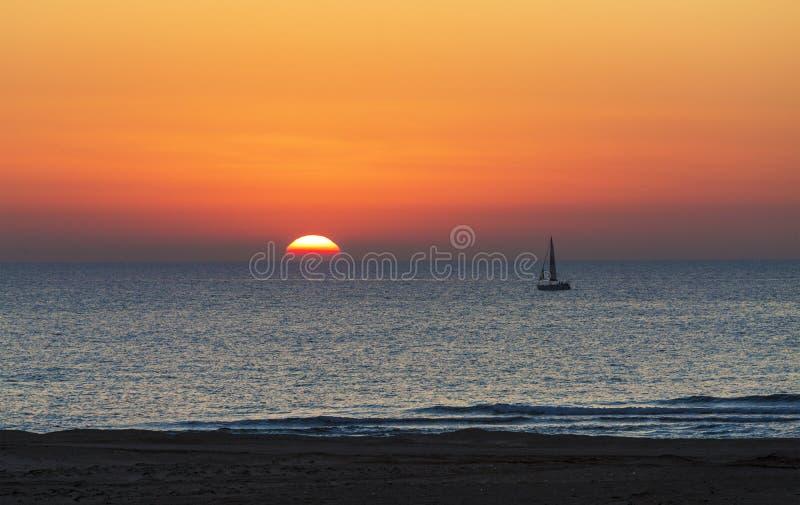 Tramonto sul mare con la siluetta di un yacht immagini stock