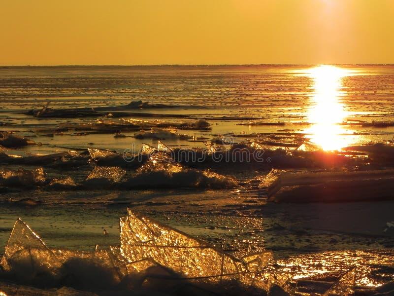 Tramonto sul mare nel ghiaccio Il sole va gi? e illumina il mare ghiacciato, gelido e soleggiato, i dettagli ed il primo piano fotografie stock