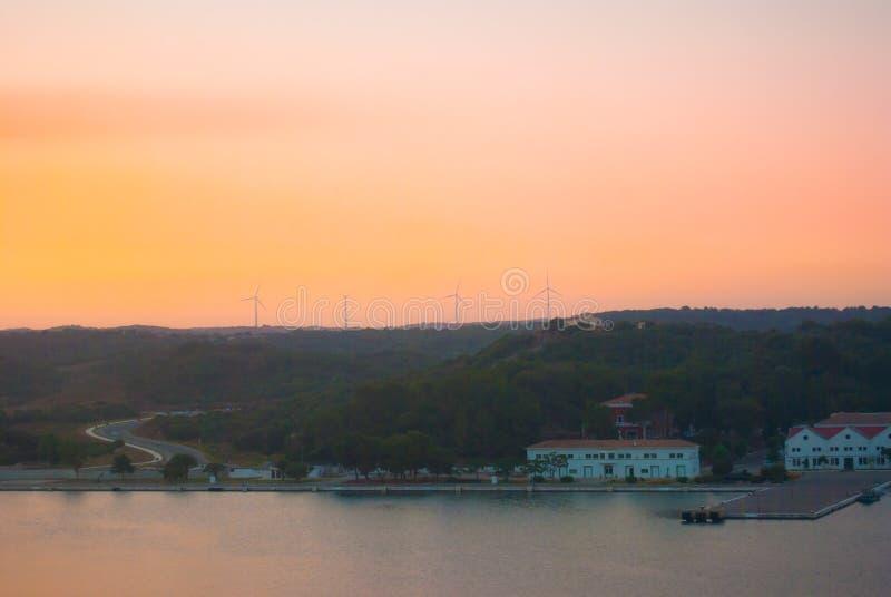 Tramonto sul porto di Mao e dei generatori eolici sul promontorio fotografia stock
