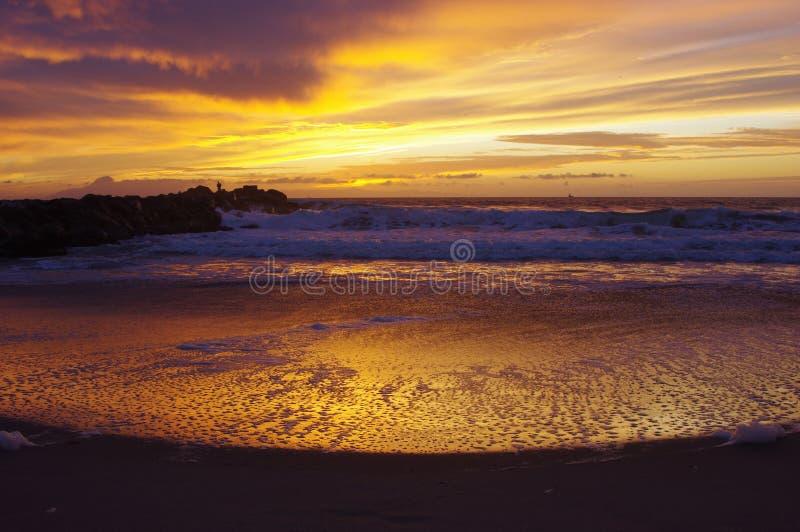 Tramonto sull'oceano, sulla spuma e sulla sabbia fotografia stock