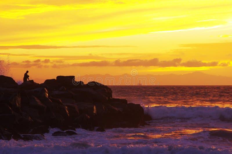 Tramonto sull'oceano, sulla spuma e sulla sabbia fotografie stock