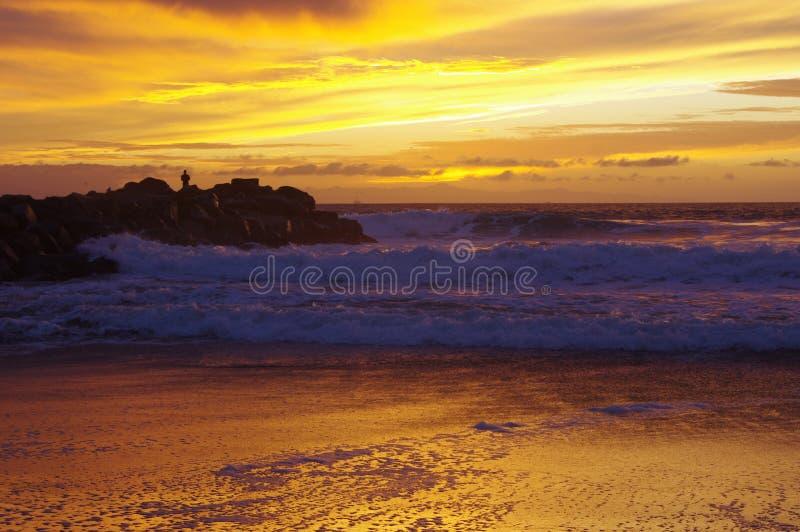 Tramonto sull'oceano, sulla spuma e sulla sabbia immagini stock