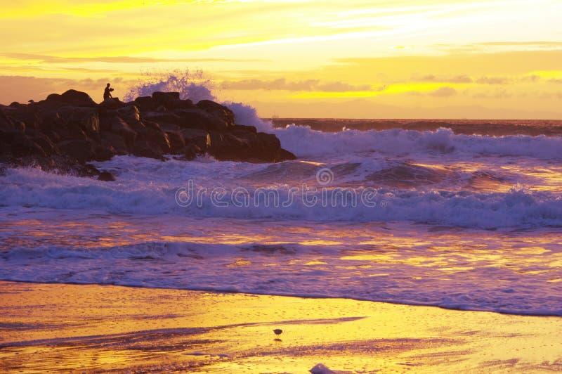 Tramonto sull'oceano, sulla spuma e sulla sabbia fotografia stock libera da diritti