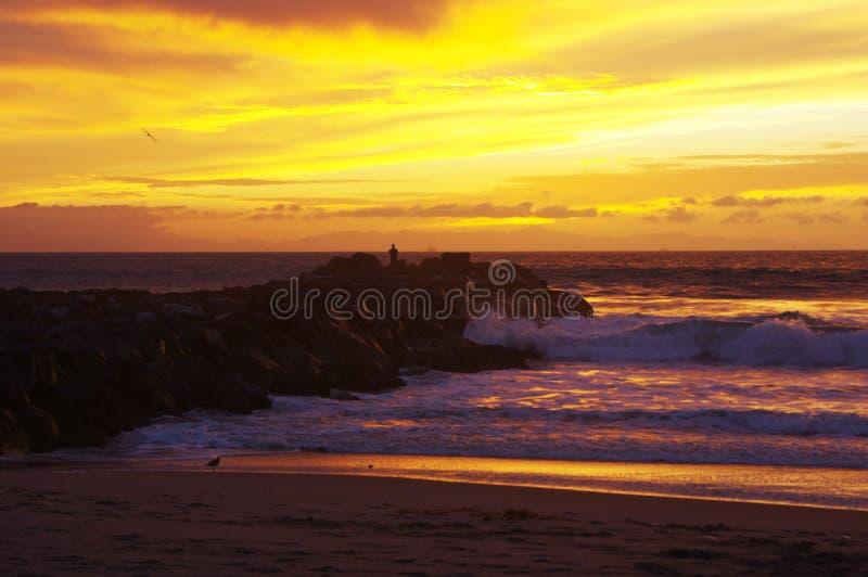 Tramonto sull'oceano, sulla spuma e sulla sabbia immagine stock