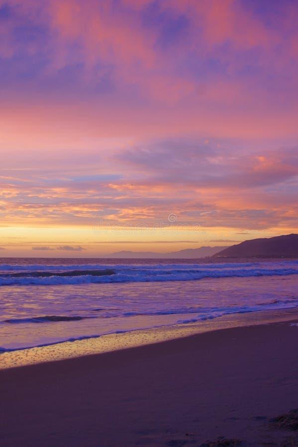 Tramonto sull'oceano, sulla spuma e sulla sabbia immagini stock libere da diritti
