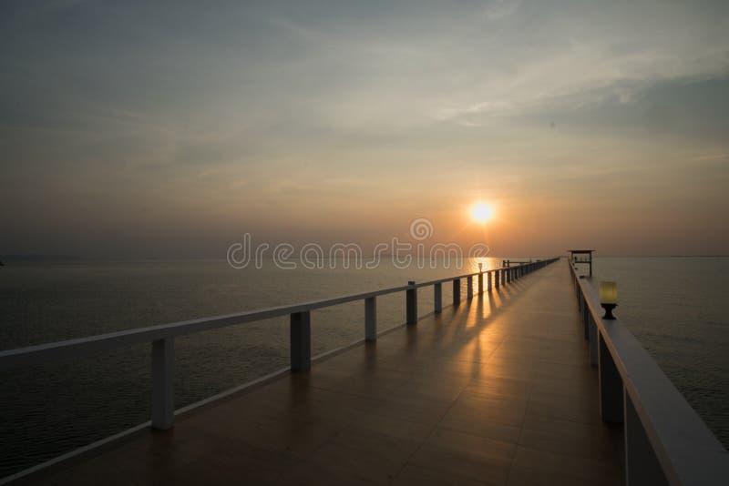 Tramonto sulla spiaggia e sul ponte fotografie stock libere da diritti