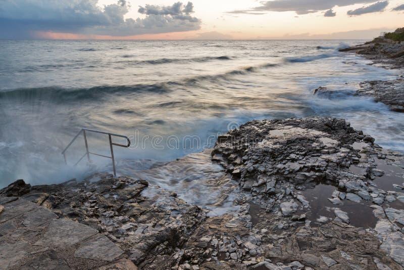 Tramonto tempestoso della spiaggia rocciosa sulla costa del mare adriatico fotografia stock