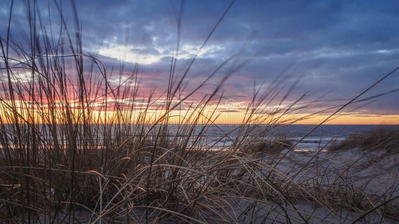 Tramonto tranquillo e variopinto alla spiaggia nel filo di Grønhoj vicino a Løkken, Danimarca fotografia stock libera da diritti