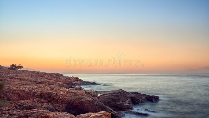 Tramonto tropicale arancio variopinto sopra una linea costiera rocciosa fotografia stock libera da diritti