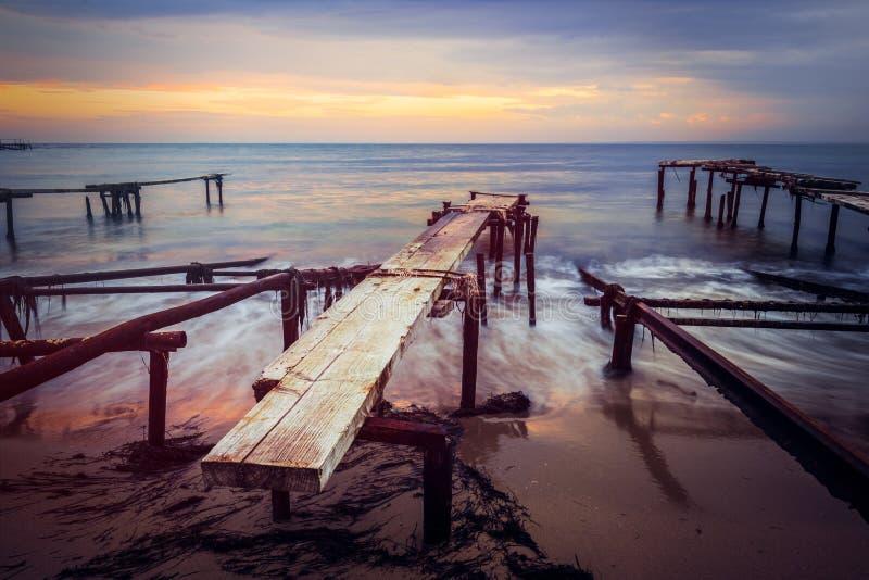 Tramonto variopinto sopra la riva di mare Vecchi ancoraggi arrugginiti della barca Effetto regolare delle onde di acqua di esposi fotografie stock