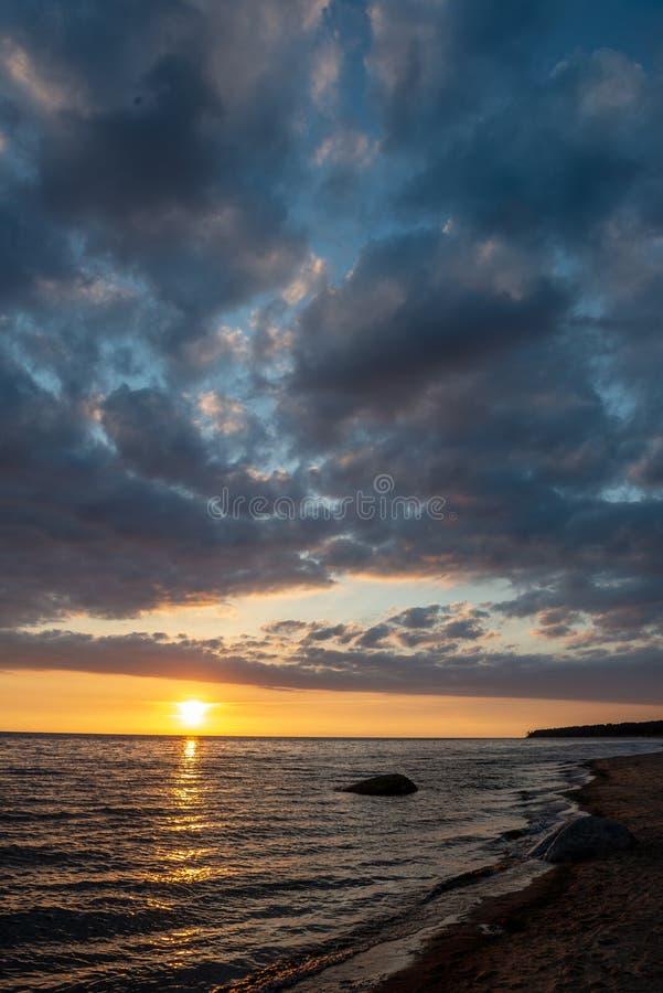 tramonto variopinto sopra la spiaggia del mare calmo con acqua blu scuro e le nuvole contrasty drammatiche fotografia stock